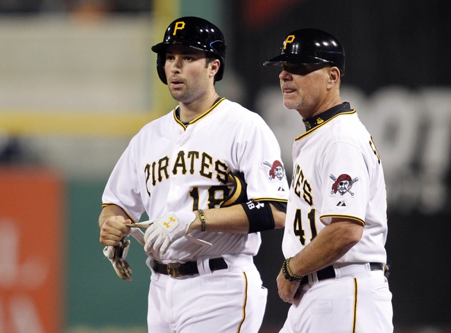Sep 18, 2013; Pittsburgh, PA, USA; Pittsburgh Pirates second baseman Neil Walker (18) at first base along side first base coach Rick Sofield (41) after Walker reached on a strike three passed ball against the San Diego Padres during the seventh inning at PNC Park. The San Diego Padres won 3-2. Mandatory Credit: Charles LeClaire-USA TODAY Sports