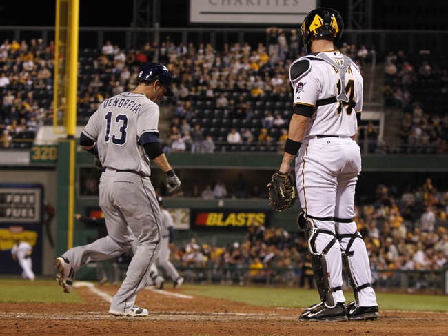 Sep 18, 2013; Pittsburgh, PA, USA; San Diego Padres right fielder Chris Denorfia (13) scores the game winning run in front of Pittsburgh Pirates catcher John Buck (14) during the ninth inning at PNC Park. The San Diego Padres won 3-2. Mandatory Credit: Charles LeClaire-USA TODAY Sports