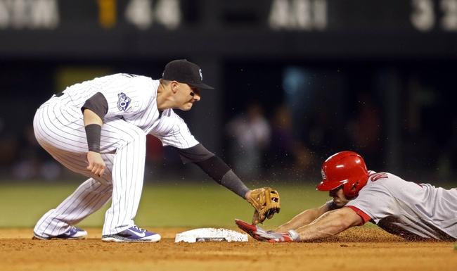 Sep 18, 2013; Denver, CO, USA; Colorado Rockies shortstop Troy Tulowitzki (left) is unable to make the tag in time as St. Louis Cardinals left fielder Matt Holiday (right) slides into second base for a double during the fifth inning at Coors Field. Mandatory Credit: Chris Humphreys-USA TODAY Sports