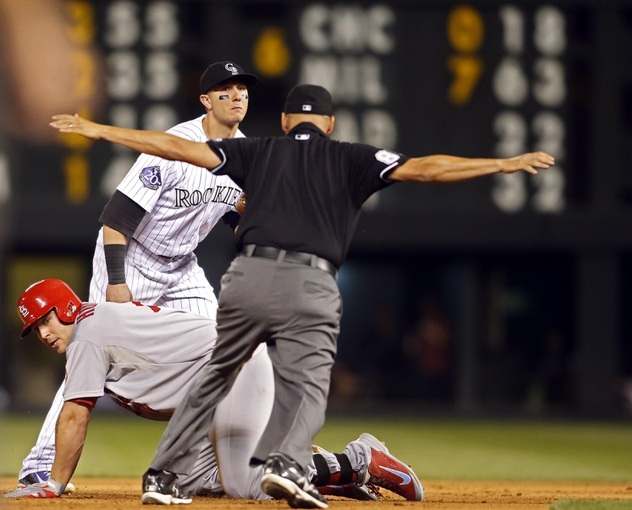 Sep 18, 2013; Denver, CO, USA; Second base umpire Bill Miller (right) signals safe after Colorado Rockies shortstop Troy Tulowitzki (2) failed to make the tag in time on a double by St. Louis Cardinals left fielder Matt Holiday (7) during the fifth inning at Coors Field. Mandatory Credit: Chris Humphreys-USA TODAY Sports
