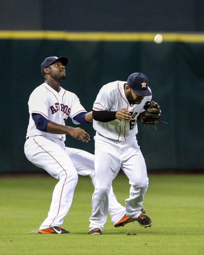 Sep 18, 2013; Houston, TX, USA; Houston Astros left fielder Chris Carter (23) and shortstop Jonathan Villar (6) are unable to catch a pop fly during the sixth inning against the Cincinnati Reds at Minute Maid Park. Mandatory Credit: Troy Taormina-USA TODAY Sports