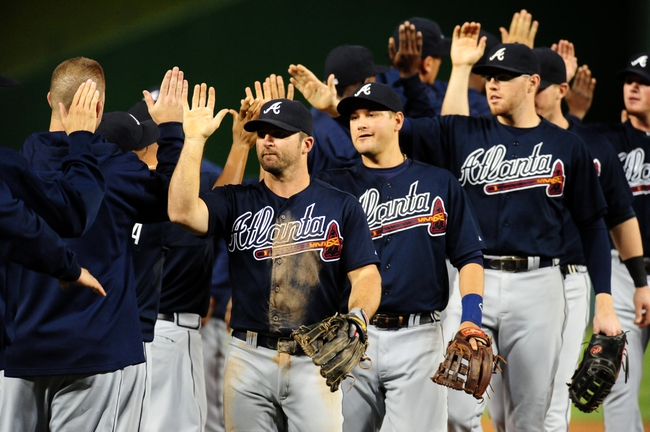 Sep 18, 2013; Washington, DC, USA; Atlanta Braves second baseman Dan Uggla (26) high fives teammates after beating the Washington Nationals 5-2 at Nationals Park. Mandatory Credit: Evan Habeeb-USA TODAY Sports