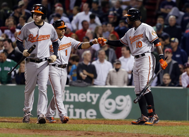 Sep 18, 2013; Boston, MA, USA; Baltimore Orioles center fielder Adam Jones (10) congratulates second baseman Brian Roberts (1) after scoring in the twelfth inning against the Boston Red Sox at Fenway Park. Mandatory Credit: David Butler II-USA TODAY Sports
