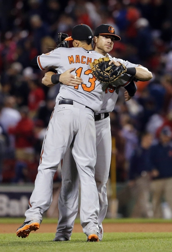 Sep 18, 2013; Boston, MA, USA; Baltimore Orioles third baseman Manny Machado (13) and first baseman Chris Davis (19) react after defeating the Boston Red Sox 5-3 at Fenway Park. Mandatory Credit: David Butler II-USA TODAY Sports