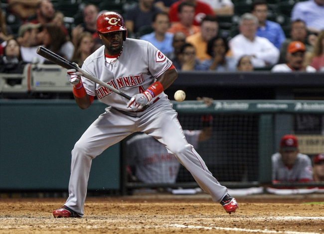 Sep 18, 2013; Houston, TX, USA; Cincinnati Reds second baseman Brandon Phillips (4) bunts the ball during the ninth inning against the Houston Astros at Minute Maid Park. Mandatory Credit: Troy Taormina-USA TODAY Sports