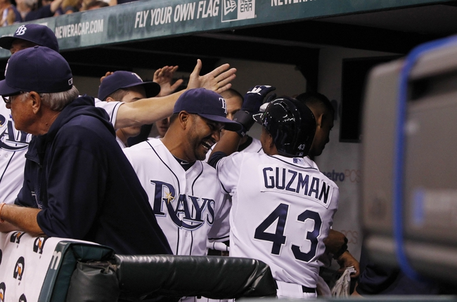 Sep 18, 2013; St. Petersburg, FL, USA; Tampa Bay Rays outfielder Freddy Guzman (43) is congratulated by teammates after scoring a run during the eleventh inning against the Texas Rangers at Tropicana Field. Mandatory Credit: Kim Klement-USA TODAY Sports