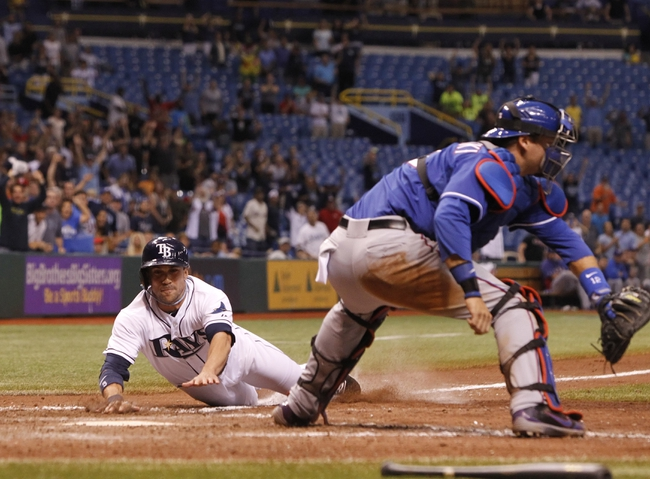 Sep 18, 2013; St. Petersburg, FL, USA; Tampa Bay Rays left fielder Sam Fuld (5) slides safely into home plate to score the winning run as Texas Rangers catcher A.J. Pierzynski (12) attempts the tag during the twelfth inning at Tropicana Field. Tampa Bay Rays defeated the Texas Rangers 4-3 in twelve innings. Mandatory Credit: Kim Klement-USA TODAY Sports