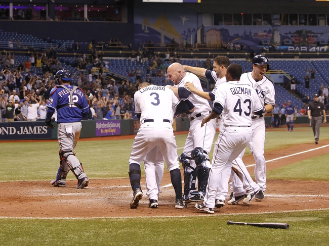 Sep 18, 2013; St. Petersburg, FL, USA; Tampa Bay Rays left fielder Sam Fuld (5) is congratulated by teammates after scoring the winning run as Texas Rangers catcher A.J. Pierzynski (12) walks off the field during the twelfth inning at Tropicana Field. Tampa Bay Rays defeated the Texas Rangers 4-3 in twelve innings. Mandatory Credit: Kim Klement-USA TODAY Sports