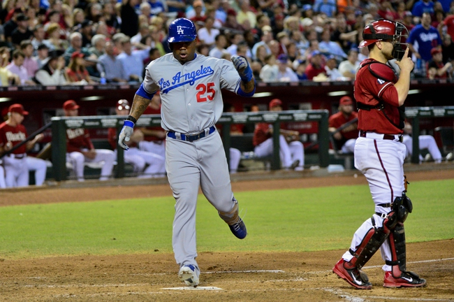 Sep 18, 2013; Phoenix, AZ, USA; Los Angeles Dodgers left fielder Carl Crawford (25) scores on single by first baseman Adrian Gonzalez (not pictured) as Arizona Diamondbacks catcher Miguel Montero (26) looks on during the fourth inning at Chase Field. Mandatory Credit: Matt Kartozian-USA TODAY Sports