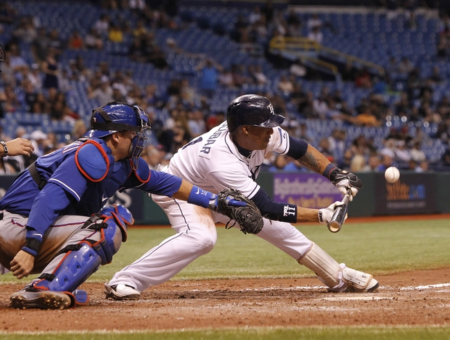 Sep 18, 2013; St. Petersburg, FL, USA; Tampa Bay Rays shortstop Yunel Escobar (11) hits a sacrifice bunt during the twelfth inning against the Texas Rangers at Tropicana Field. Tampa Bay Rays defeated the Texas Rangers 4-3 in twelve innings. Mandatory Credit: Kim Klement-USA TODAY Sports