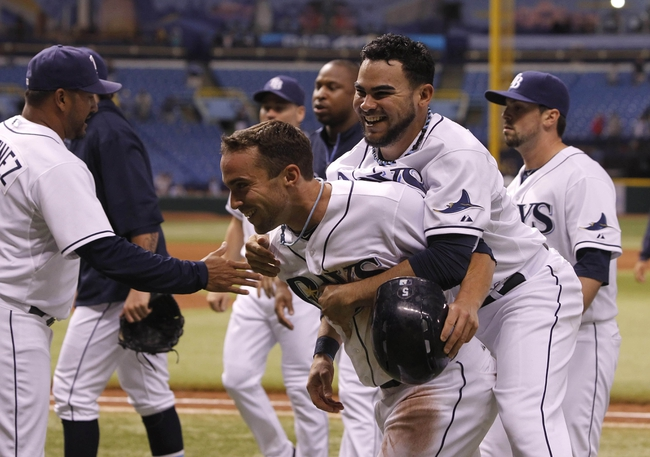 Sep 18, 2013; St. Petersburg, FL, USA; Tampa Bay Rays relief pitcher Alex Torres (54) jumps on the back of Tampa Bay Rays left fielder Sam Fuld (5) after he scored the winning run during the twelfth inning against the Texas Rangers at Tropicana Field. Tampa Bay Rays defeated the Texas Rangers 4-3 in twelve innings. Mandatory Credit: Kim Klement-USA TODAY Sports