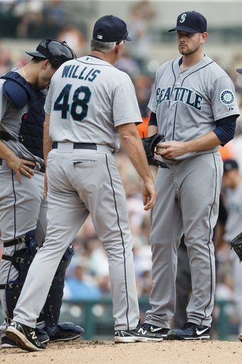 Sep 18, 2013; Detroit, MI, USA; Seattle Mariners pitching coach Carl Willis (48) talks to starting pitcher James Paxton (65) after he walks in a run for the Detroit Tigers at Comerica Park. Mandatory Credit: Rick Osentoski-USA TODAY Sports