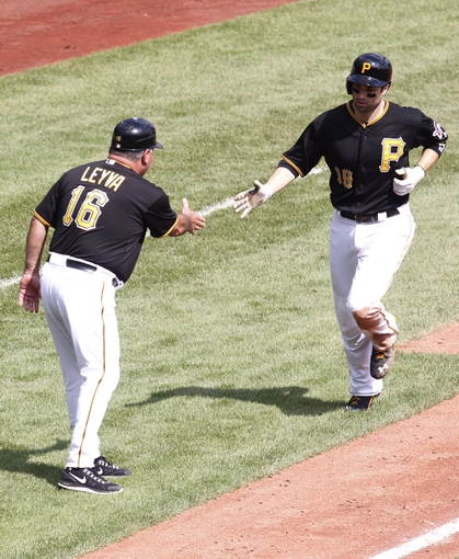 Sep 19, 2013; Pittsburgh, PA, USA; Pittsburgh Pirates third base coach Nick Leyva (16) greets second baseman Neil Walker (18) after Walker hit a two run  home run against the San Diego Padres during the fourth inning at PNC Park. Mandatory Credit: Charles LeClaire-USA TODAY Sports