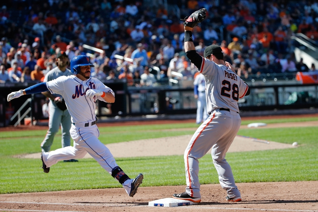 Sep 19, 2013; New York, NY, USA;  San Francisco Giants first baseman Buster Posey (28) has New York Mets shortstop Omar Quintanilla (3) out during the fifth inning at Citi Field. Mandatory Credit: Anthony Gruppuso-USA TODAY Sports
