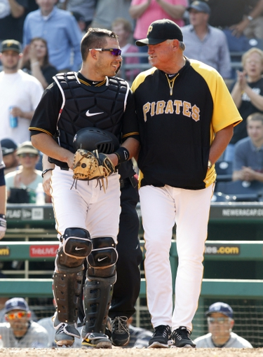 Sep 19, 2013; Pittsburgh, PA, USA; Pittsburgh Pirates catcher Tony Sanchez (left) shares a laugh with manager Clint Hurdle (13) after Sanchez tumbled into the San Diego Padres dugout to record an out during the eighth inning at PNC Park. The Pittsburgh Pirates won 10-1. Mandatory Credit: Charles LeClaire-USA TODAY Sports