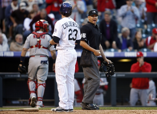 Sep 19, 2013; Denver, CO, USA; Colorado Rockies left fielder Charlie Culberson (23) argues a strikeout with home plate umpire Vic Carapazza (45) during the thirteenth inning against the St. Louis Cardinals at Coors Field. The Rockies won 7-6 in 15 innings.  Mandatory Credit: Chris Humphreys-USA TODAY Sports