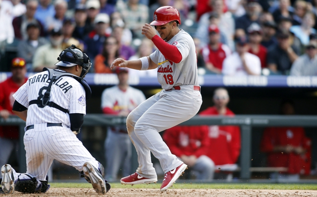 Sep 19, 2013; Denver, CO, USA; St. Louis Cardinals center fielder Jon Jay (19) is tagged out by Colorado Rockies catcher Yorvit Torrealba (8)  attempting to steal home plate after a wild pitch during the ninth inning at Coors Field.  The Rockies won 7-6 in 15 innings.  Mandatory Credit: Chris Humphreys-USA TODAY Sports