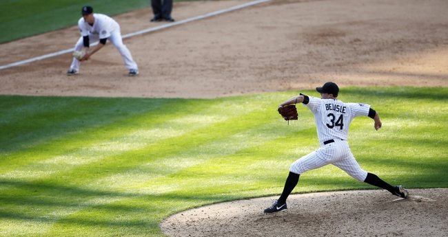 Sep 19, 2013; Denver, CO, USA; Colorado Rockies pitcher Matt Belisle (34) delivers a pitch during the tenth inning against the St. Louis Cardinals at Coors Field. The Rockies won 7-6 in 15 innings.  Mandatory Credit: Chris Humphreys-USA TODAY Sports