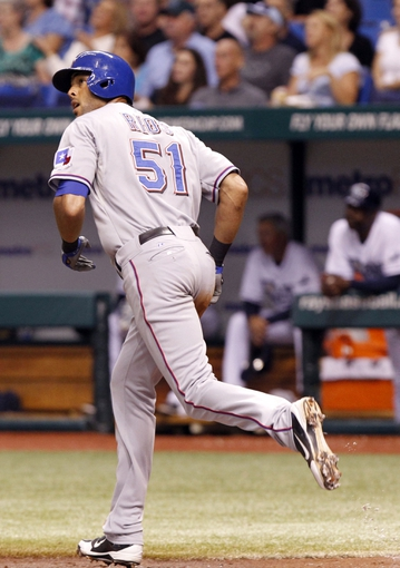 Sep 19, 2013; St. Petersburg, FL, USA; Texas Rangers right fielder Alex Rios (51) looks on at his ball it goes into the outfield and he hits a solo home run against the Tampa Bay Rays during the third inning at Tropicana Field. Mandatory Credit: Kim Klement-USA TODAY Sports