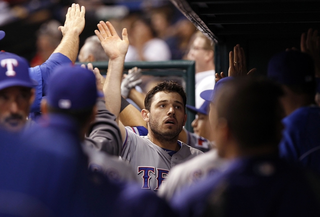 Sep 19, 2013; St. Petersburg, FL, USA; Texas Rangers second baseman Ian Kinsler (5) is congratulated by teammates in the dugout after he scored a run during the fourth inning against the Tampa Bay Rays at Tropicana Field. Mandatory Credit: Kim Klement-USA TODAY Sports