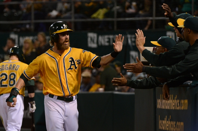 September 19, 2013; Oakland, CA, USA; Oakland Athletics right fielder Josh Reddick (16) is congratulated for scoring on a sacrifice fly by catcher Stephen Vogt (21, not pictured) against the Minnesota Twins during the fourth inning at O.co Coliseum. Mandatory Credit: Kyle Terada-USA TODAY Sports