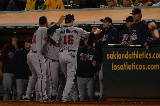September 19, 2013; Oakland, CA, USA; Minnesota Twins left fielder Josh Willingham (16) is congratulated for scoring on a RBI-single shortstop Pedro Florimon (25, not pictured) against the Oakland Athletics during the sixth inning at O.co Coliseum. Mandatory Credit: Kyle Terada-USA TODAY Sports