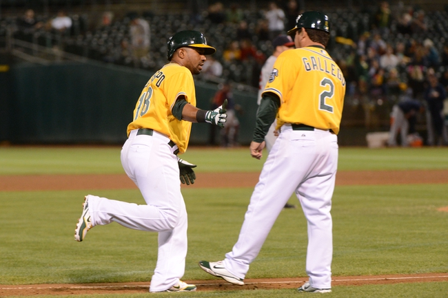 September 19, 2013; Oakland, CA, USA; Oakland Athletics second baseman Alberto Callaspo (18) is congratulated by third base coach Mike Gallego (2) for hitting a solo home run against the Minnesota Twins during the sixth inning at O.co Coliseum. Mandatory Credit: Kyle Terada-USA TODAY Sports
