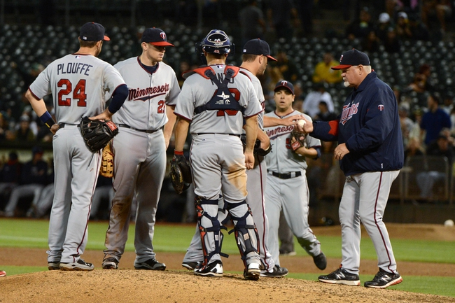 September 19, 2013; Oakland, CA, USA; Minnesota Twins manager Ron Gardenhire (35, far right) receives the baseball from relief pitcher Brian Duensing (52) in a pitching change against the Oakland Athletics during the sixth inning at O.co Coliseum. Mandatory Credit: Kyle Terada-USA TODAY Sports