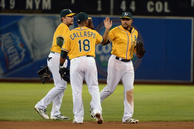 September 19, 2013; Oakland, CA, USA; Oakland Athletics center fielder Coco Crisp (4, right) celebrates with second baseman Alberto Callaspo (18) after the game against the Minnesota Twins at O.co Coliseum. The Athletics defeated the Twins 8-6. Mandatory Credit: Kyle Terada-USA TODAY Sports