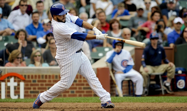 Sep 20, 2013; Chicago, IL, USA; Chicago Cubs catcher Dioner Navarro hits a home run in the 8th inning of their game against the Atlanta Braves at Wrigley Field. Mandatory Credit: Matt Marton-USA TODAY Sports