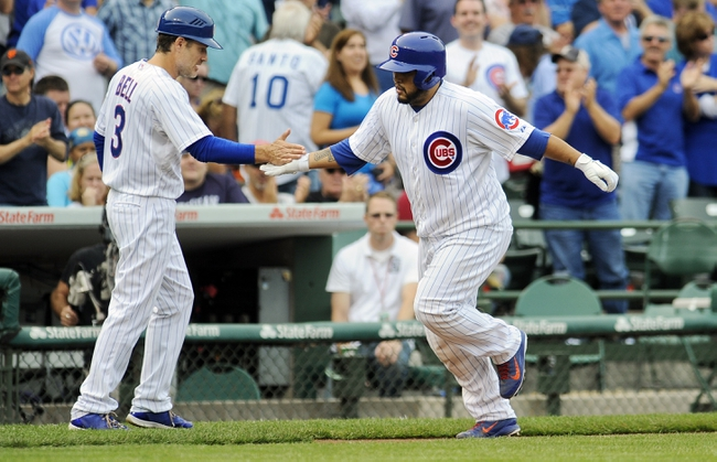 Sep 20, 2013; Chicago, IL, USA; Chicago Cubs catcher Dioner Navarro gets congratulations from third base coach David Bell after he hits a home run in the 8th inning of their game against the Atlanta Braves at Wrigley Field. Mandatory Credit: Matt Marton-USA TODAY Sports
