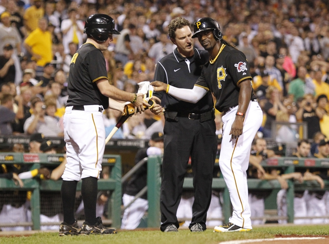 Sep 20, 2013; Pittsburgh, PA, USA; Pittsburgh Pirates center fielder Andrew McCutchen (right) reacts as a trainer checks on him after McCutchen was hit by a pitch by the Cincinnati Reds during the eighth inning at PNC Park. The Cincinnati Reds won 6-5 in ten innings. Mandatory Credit: Charles LeClaire-USA TODAY Sports