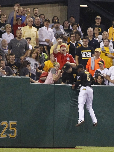 Sep 20, 2013; Pittsburgh, PA, USA; Pittsburgh Pirates left fielder Starling Marte (6) and fans react after a solo home run by Cincinnati Reds first baseman Joey Votto (not pictured) lands in the stands during the tenth inning at PNC Park. The Cincinnati Reds won 6-5 in ten innings. Mandatory Credit: Charles LeClaire-USA TODAY Sports