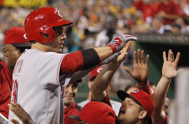 Sep 20, 2013; Pittsburgh, PA, USA; Cincinnati Reds first baseman Joey Votto (19) is greeted at the dugout after hitting a solo home run against the Pittsburgh Pirates during the tenth inning at PNC Park. The Cincinnati Reds won 6-5 in ten innings.  Mandatory Credit: Charles LeClaire-USA TODAY Sports