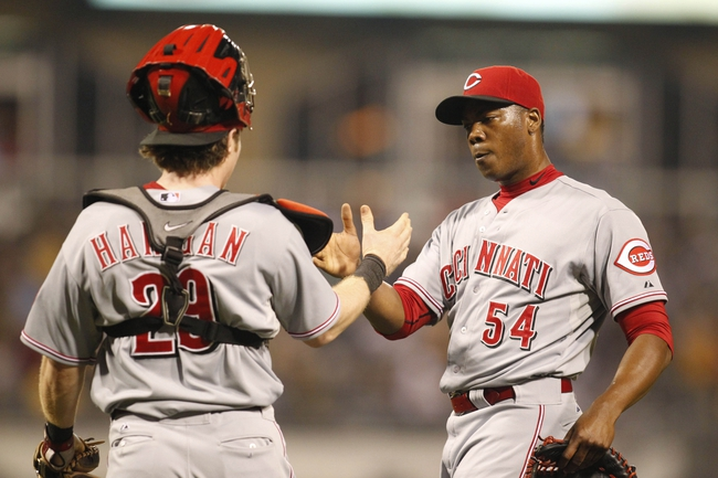 Sep 20, 2013; Pittsburgh, PA, USA; Cincinnati Reds catcher Ryan Hanigan (29) and relief pitcher Aroldis Chapman (54) celebrate after defeating the Pittsburgh Pirates during the tenth inning at PNC Park. The Cincinnati Reds won 6-5 in ten innings. Mandatory Credit: Charles LeClaire-USA TODAY Sports