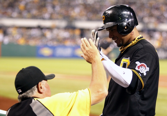 Sep 20, 2013; Pittsburgh, PA, USA; Pittsburgh Pirates manager Clint Hurdle (13) greets left fielder Jose Tabata (31) after Tabata drove in a run against the Cincinnati Reds during the seventh inning at PNC Park. The Cincinnati Reds won 6-5 in ten innings. Mandatory Credit: Charles LeClaire-USA TODAY Sports
