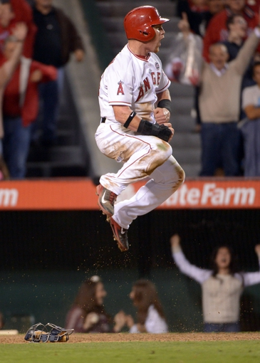Sep 20, 2013; Anaheim, CA, USA; Los Angeles Angels right fielder Kole Calhoun (56) celebrates after scoring the winning run in the 11th inning against the Seattle Mariners at Angel Stadium. The Angels defeated the Mariners 3-2 in 11 innings. Mandatory Credit: Kirby Lee-USA TODAY Sports