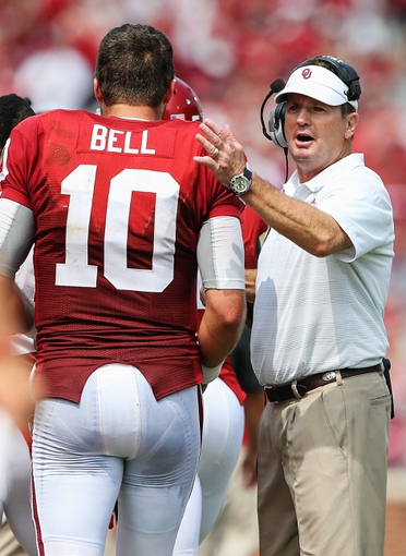 Sep 14, 2013; Norman, OK, USA; Oklahoma Sooners head coach Bob Stoops congratulates quarterback Blake Bell (10)  during the game against the Tulsa Golden Hurricane at Gaylord Family - Oklahoma Memorial Stadium. Oklahoma won 51-20. Mandatory Credit: Kevin Jairaj-USA TODAY Sports