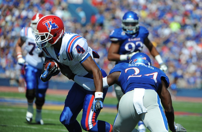 Sep 21, 2013; Lawrence, KS, USA; Louisiana Tech Bulldogs wide receiver Sterling Griffin (4) is tackled by Kansas Jayhawks cornerback JaCorey Shepherd (24) in the first half at Memorial Stadium. Mandatory Credit: John Rieger-USA TODAY Sports