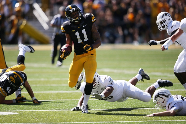 Sep 21, 2013; Iowa City, IA, USA; USA Iowa Hawkeyes wide receiver K. martin-Manley (11) returns in second punt for a touchdown in the first half against the Western Michigan Broncos at Kinnick Stadium. Mandatory Credit: Reese Strickland-USA TODAY Sports