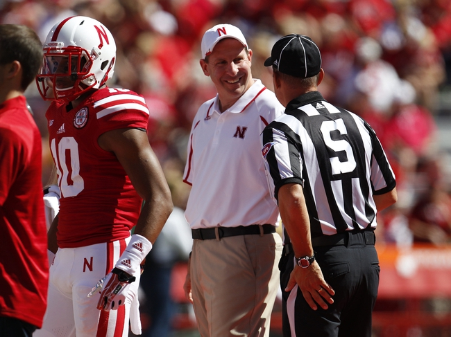 Sep 21, 2013; Lincoln, NE, USA; Nebraska Cornhuskers head coach Bo Pelini talks with side judge Frank Steratore prior to the game against the South Dakota State Jackrabbits at Memorial Stadium. Mandatory Credit: Bruce Thorson-USA TODAY Sports