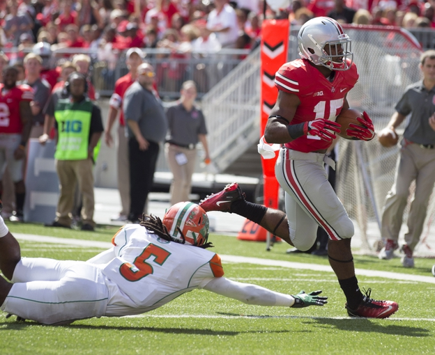 Sep 21, 2013; Columbus, OH, USA; Ohio State Buckeyes running back Ezekiel Elliott (15) evades diving Florida A&M Rattlers defensive back Patrick Aiken (5) at Ohio Stadium. Ohio State won the game 76-0. Mandatory Credit: Greg Bartram-USA TODAY Sports
