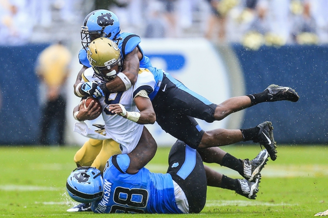 Sep 21, 2013; Atlanta, GA, USA; Georgia Tech Yellow Jackets running back Tony Zenon (9) is tackled by North Carolina Tar Heels defensive end Justin Thomason (98) and cornerback Jabari Price (4) in the second half at Bobby Dodd Stadium. Georgia Tech won 28-20. Mandatory Credit: Daniel Shirey-USA TODAY Sports