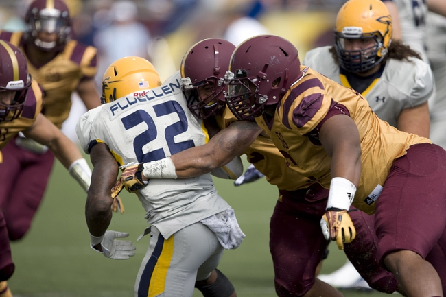 Sep 21, 2013; Mount Pleasant, MI, USA; Toledo Rockets running back David Fluellen (22) gets tackled by the Central Michigan Chippewas defense during the third quarter at Kelly/Shorts Stadium. Rockets beat the Chippewas 38-17. Mandatory Credit: Raj Mehta-USA TODAY Sports