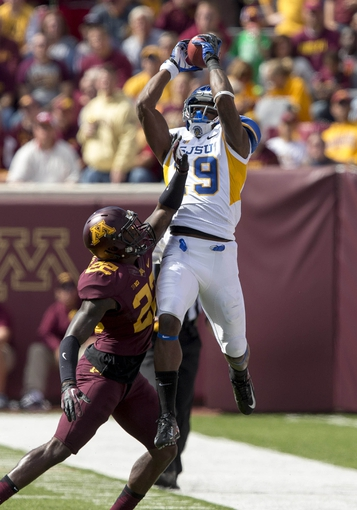 Sep 21, 2013; Minneapolis, MN, USA; San Jose State Spartans wide receiver Kyle Nunn (19) jumps over Minnesota Golden Gophers defensive back Jeremy Baltazar (22) to catch a pass in the second half at TCF Bank Stadium. The Gophers won 43-24. Mandatory Credit: Jesse Johnson-USA TODAY Sports