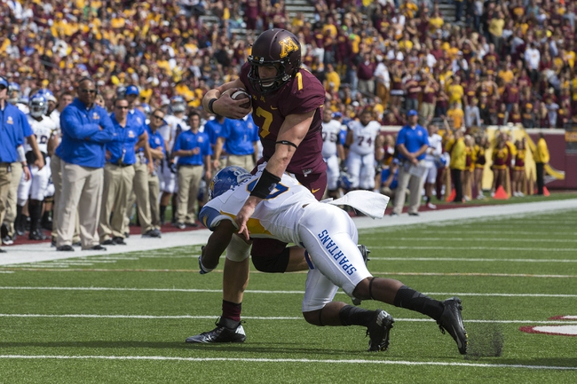 Sep 21, 2013; Minneapolis, MN, USA; Minnesota Golden Gophers quarterback Mitch Leidner (7) rushes with the ball as he gets tackled by San Jose State Spartans safety Damon Ogburn (6) at TCF Bank Stadium. The Gophers won 43-24. Mandatory Credit: Jesse Johnson-USA TODAY Sports