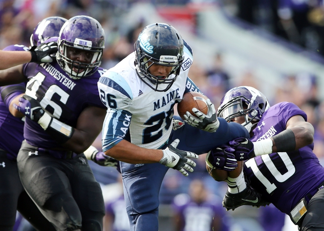 Sep 21, 2013; Evanston, IL, USA;  Maine Black Bears running back Nigel Jones (26) is tackled by Northwestern Wildcats safety Traveon Henry (10) and linebacker Damien Proby (46) during the second quarter at Ryan Field.  Mandatory Credit: Jerry Lai-USA TODAY Sports