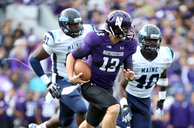 Sep 21, 2013; Evanston, IL, USA; Northwestern Wildcats quarterback Trevor Siemian (13) runs away from Maine Black Bears defensive lineman Jonathan Lewis (91) and linebacker Christophe Mulumba (40) during the second quarter at Ryan Field.  Mandatory Credit: Jerry Lai-USA TODAY Sports