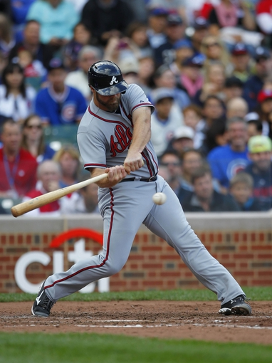 Sep 21, 2013; Chicago, IL, USA; Atlanta Braves catcher Evan Gattis (24) hits an RBI single in the fourth inning against the Chicago Cubs at Wrigley Field. Mandatory Credit: Dennis Wierzbicki-USA TODAY Sports