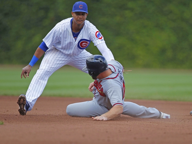 Sep 21, 2013; Chicago, IL, USA; Atlanta Braves catcher Evan Gattis (24) slides safely into second base under the tag of Chicago Cubs shortstop Starlin Castro (13) in the fourth inning at Wrigley Field. Mandatory Credit: Dennis Wierzbicki-USA TODAY Sports